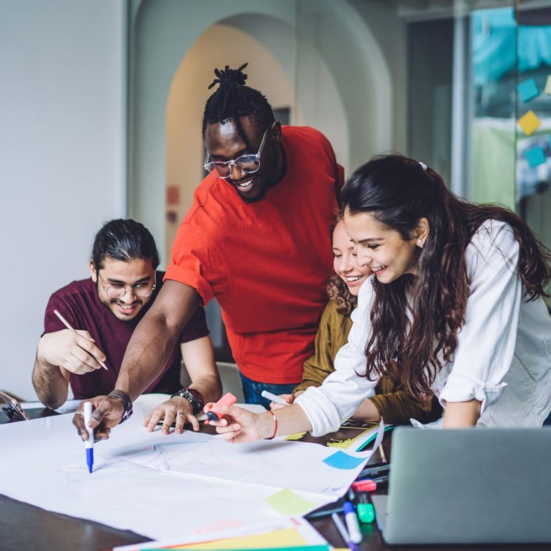 Smiling African American man drawing on paper poster while coworking with diverse group mates and creating new project in team